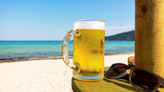 Pint of cold beer on top of the beach table
